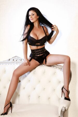Paddington Escort Fanny, Slim & busty brunette. Wearing BDSM black bra and panties sitting down at 24hr London Escorts Agency