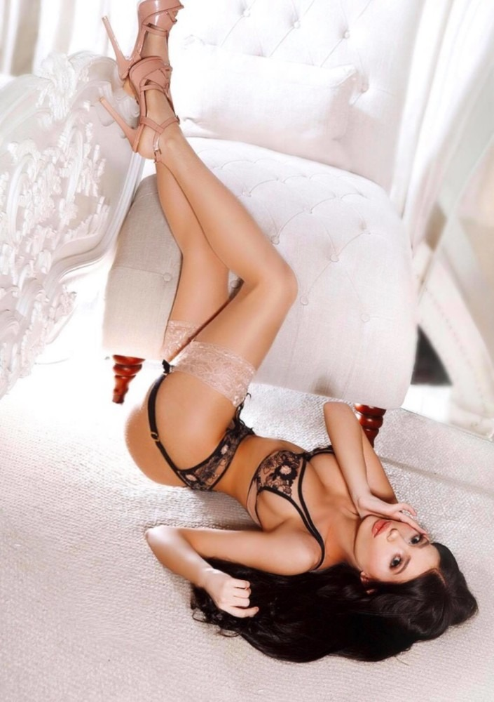 Mayfair Escort Jazz Slender & Slim laying down in black lingerie at 24hr London Escorts Agency