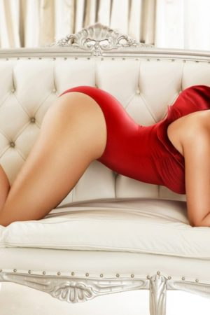 Busty Gloucester Road Escort Clarissa. Wearing Sexy red body suit at 24hr London Escorts Agency