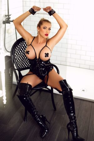 BDSM Marble Arch Escort Denny Blonde Busty & Slim. Topless in leather handcuffs and thigh length at 24hr London Escorts Agency