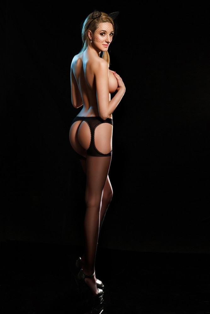 Bayswater Escort Eva Slim and Slender blonde. Wearing Red lingerie topless at 24hr London Escorts Agency