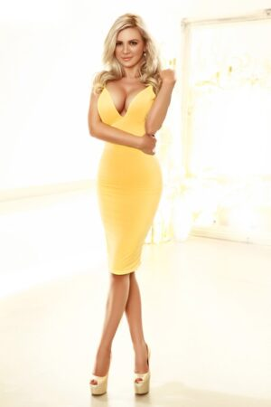 Kngightsbridge Escort Evelyn. Slim and busty Blonde babe. Wearing Yellow bodycon dress, at 24hr London Escorts Agency