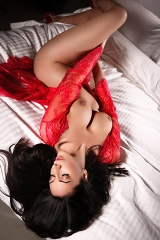 Bayswater Escort Lora Slim and Busty model. Wearing red lace lingerie, laying down, at 24hr Lonndon Escorts Agency