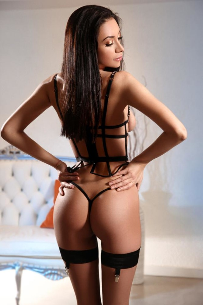 Bayswater Escort Lora Slim and Busty model. Wearing black BDSM body suit, 24hr Lonndon Escorts Agency