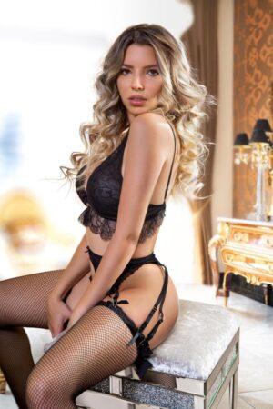 Mayfair Escort Lulu. Alluring Blonde Brazilian model. Wearing black lace panties and bra, at 24hr London Escorts Agency
