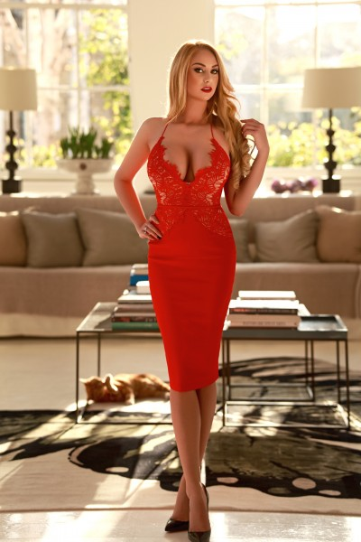 Bond Street Escort Michelle. Sexy Blonde Busty vixen. Wearing red cocktail dress, at 24hr London Escorts Agency