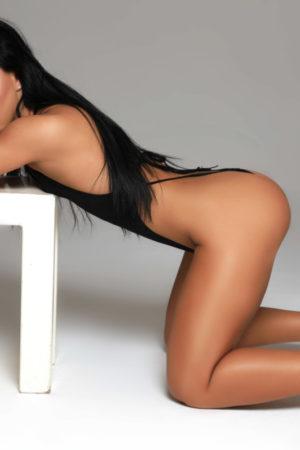 Gloucester Road escort Zenaida wearing dazzling black bathing suit bent over at 24hr London Escorts