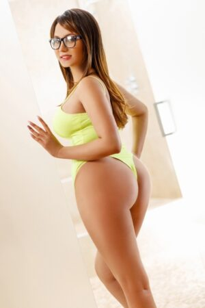 Carina Sexy Brunette Busty escort in London wearing green revealing body suit at 24hr London Escorts