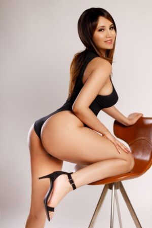 Carina Sexy Brunette Busty escort in London wearing black body suit at 24hr London Escorts