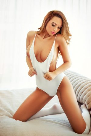South Kensington Escort Anabelle. Slim and Busty. Wearing sexy white swim suit at 24hr London Escorts Agency