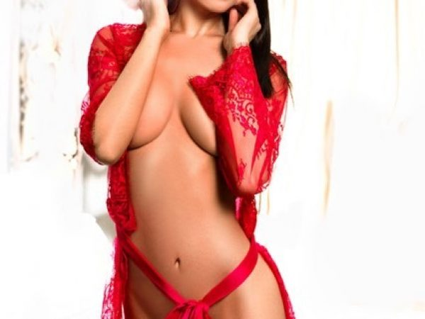 Bayswater Escort Lora Slim and Busty model. Wearing red lace lingerie, and Santa hat, at 24hr Lonndon Escorts Agency