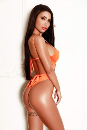 South Kensington Escort Natalia wearing revealing tangerine swim suit at 24hr London Escorts Agency